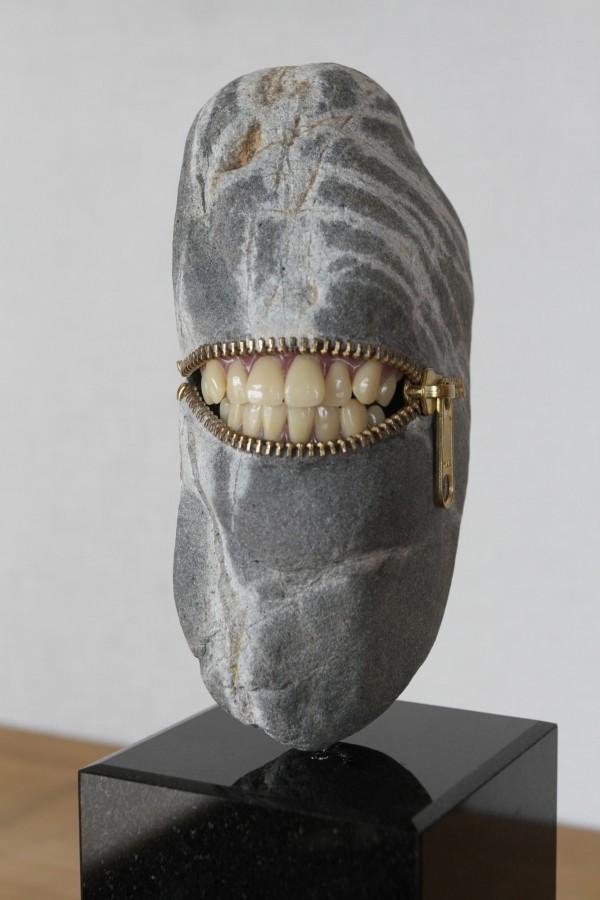 歯を見せて笑う石